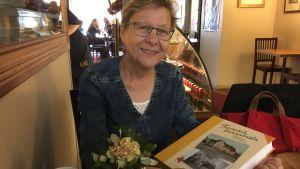 Riitta Lehtonen sitter på ett café och håller boken Terveisiä sairaalasta i sin hand.