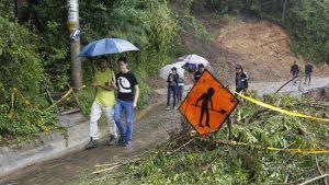 Människor går längs en väg som är delvis avskuren av bråte efter en storm i Costa Rica.