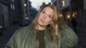 Sanna Helander ruffsar till sitt hår. Har en grön bomberjacka på sig.