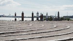 Miniatyrfyrar i havsmiljö, i förgrunden en labyrint gjord av sand och sten.