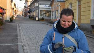 En kvinna som tittar på sin mobiltelefon. Hon heter Susanna Virtanen.