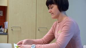 Närvårdare Johanna Danielsson sitter vid ett bord och skriver.