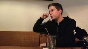 Kevin Kühnert sitter i en soffa och lutar på sin armbåge.