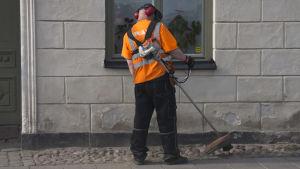 En person står med ryggen till och trimmar gräs utanför ett stenhus med en trimmer. Orange skjorta, reflex, hörselskydd. Sommar.