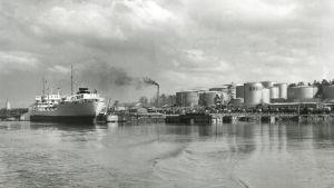 Oljehamn: Oljecisterner intill strand, stort lastfartyg vid brygga.