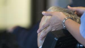 Hemvårdare berör äldre klients hår.