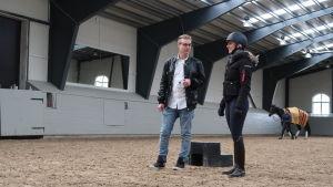 en kvinna med ridhjälm och en man i svart rock diskuterar mitt i ett ridhus. En häst blir ledd i bakgrunden