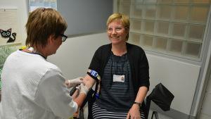 Planeringschef Pia Wik sitter i blodprovsstolen. Maria Korvo håller i nålen.