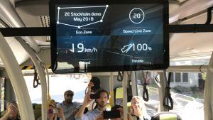 Flera personer fotar en tv-skärm inne i en buss. Skärmen visar hur bussens hastighet och hur mycket föraren gasar.