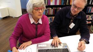 Raimo Anttila neuvoo kirjastossa Irma Pantzaria tietokoneen käytössä.