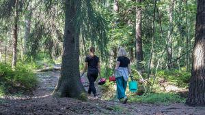 Kaksi marjanpoimijaa kävelee metsässä