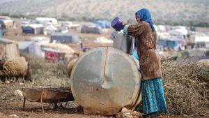 Flyktingkvinna i norra Syrien fyller på en hink med vatten i ett flyktingläger i provinsen Idlib.