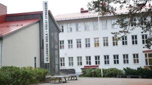 En stor skola i vit betong och rött tak. Många fönster. Står Källhagens skola och Virkby gymnasium.
