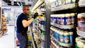 Työntelijä hyllyttää alkoholijuomia K- supermarket Kampissa, Helsingissä.