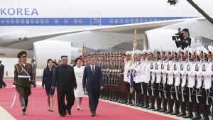 Moon Jae-In och Kim Jong-Un inspekterar hederskompaniet på flygplatsen i Pyongyang