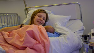 Anna Ahlnäs ligger i en sjukhussäng med sin nyfödda dotter i famnen.