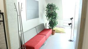 En soffa med röd sittdel och grå ryggdel.