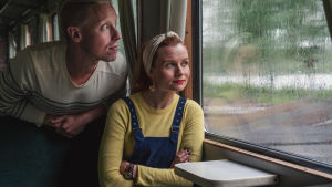 Juontajat Nicke Aldén ja Hannamari Hoikkala vanhan raidebussin penkillä, katsovat sateen raidoittaman ikkunan läpi ulos.