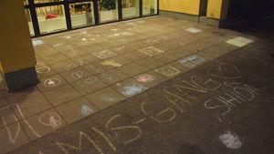 bokstäver ritade på marken invid hus