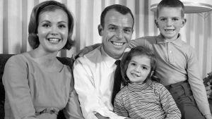 Svartvit bild av familj, pappa mamma syster och bror ler mot kameran