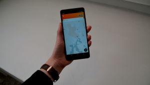 En hand som håller i en smart telefon med mobilapplikationen Kyyti