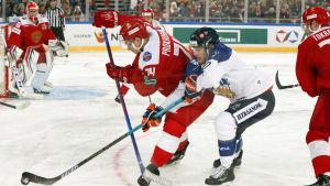 Niko Ojamäki kämpar om pucken mot två ryska spelare