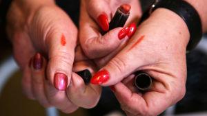 Tre händer visar upp rött nagellack på naglarna och streck av ett rött läppstift på tummen.