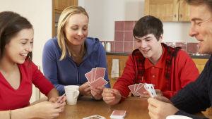 En familj med två tonårsbarn sitter runt ett bord och spelar kortspel