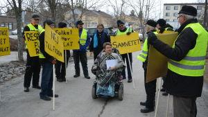 En kvinna i motoriserad rullstol kommer fram bland en liten grupp personer som håller gula plakat med sloganer mot en kommunsammanslagning.