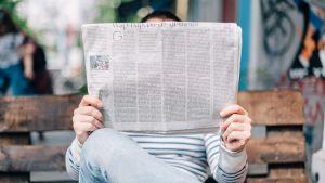 En person sitter på en parkbänk och läser nyheter.