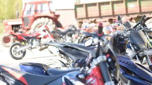 Mopeder och en traktor parkerade i Ekenäs högstadieskola. på parkeringen.