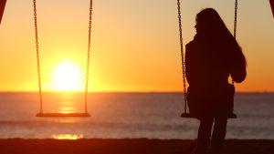 en kvinna sitter på en gunga vid stranden, det är solnedgång. Gungan bredvid henne är tom.
