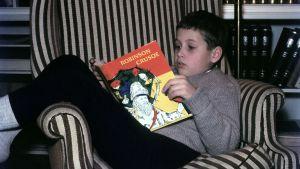 "En ung kille läser ""Robinson Crusoe""."