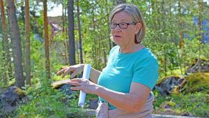 Kvinna står och förklarar något med händerna i en tallskog.