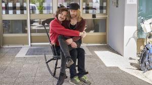 Gösta (Vilhelm Blomgren) sitter i en gungstol med sin pappa (Mattias Silvell) i famnen.