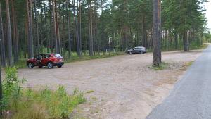 Parkeringsplats av sand med ett par bilar.
