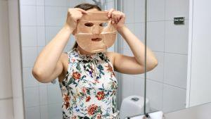 En kvinna som håller upp en ansiktsmask framför ansiktet