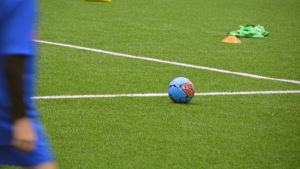 En boll på en konstgräsplan. Silhuett av ett barn i främre vänstra kanten.