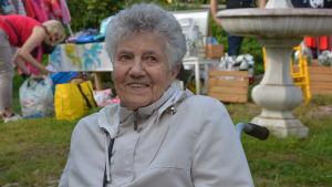 Äldre dam sitter och ler förväntansfullt på en lummig innergård.