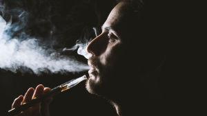 Person som röker en e-cigarett