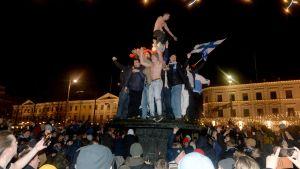 Fans som står på statyn Havis Amanda med en flagga för att fira.