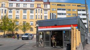 Metroasema, jonka ovesta kävelee ihmisiä aukiolle, jossa on myös poliisi sekä poliisiauto.