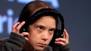 Yrmeä Greta Thunberg kuulokkeet korvilla.