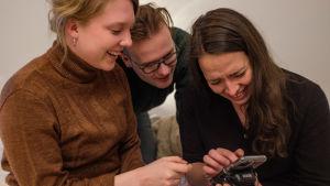 Onerva Hannula, Veikka Heinonen ja Satu-Tuuli Karhu katsovat nauraen puhelinta.
