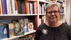 Barnboksforskare Mia Österlund och muminhyllan.