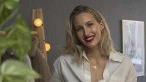 En blond kvinna iklädd vit skjorta. Hon ler.
