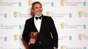 Joaquin Phoenix poserar med sitt pris på Bafta-galan.