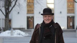 Äldre, vit man i plommonstop står framför Vasa stadsbibliotek.