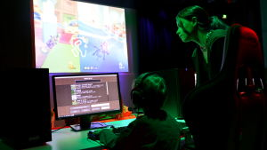 Ung kvinna instruerar ett barn vid en dator.