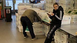 En kvinna lutar mot ett bord och en man böjer sig över en plastlåda med matvaror.
